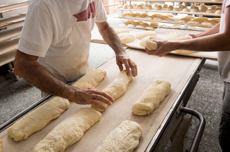 Panettieri che mettono pane ad una banda per il forno fotografia stock