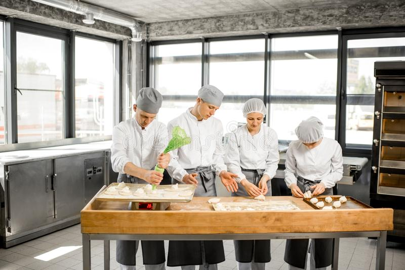 Panettieri che producono i panini alla fabbricazione immagine stock libera da diritti