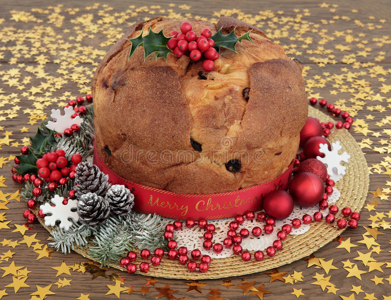 Panettone Christmas Cake. Panettone christams cake with holly, decorations and winter greenery over oak background with gold stars royalty free stock image