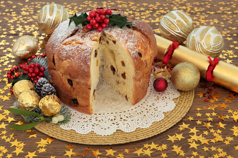 Panettone Christmas Cake. With gold bauble decorations, holly and winter flora over oak background with stars stock photography