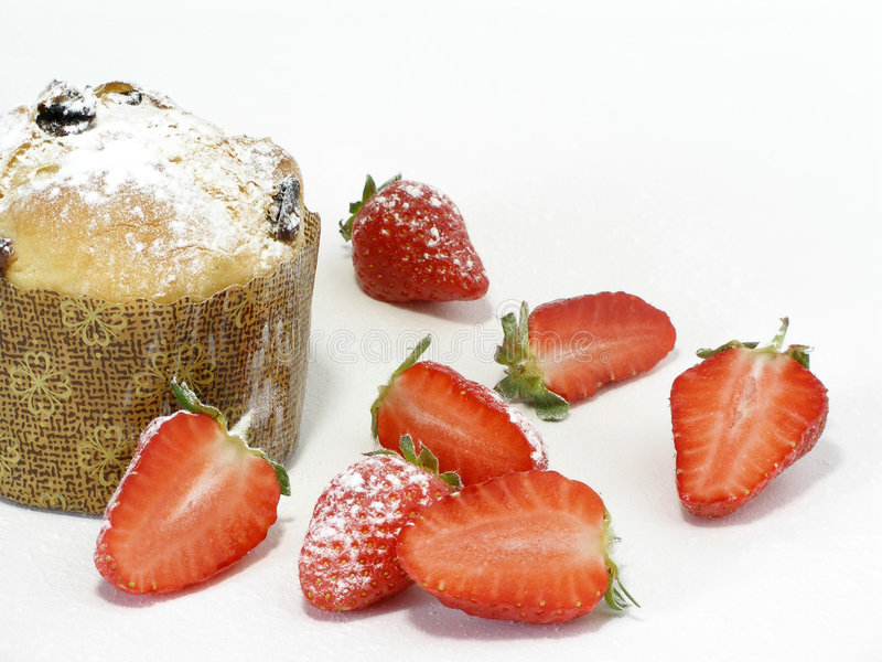 Panettoni and strawberries with icing sugar. Panettonin with strawberries and icing sugar to be eaten royalty free stock photos