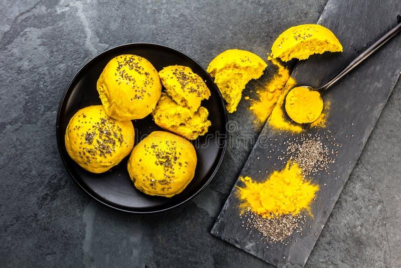Panez les petits pains d'hamburger avec le safran des Indes et le chia de superfoods sur le fond d'ardoise Vue supérieure images stock