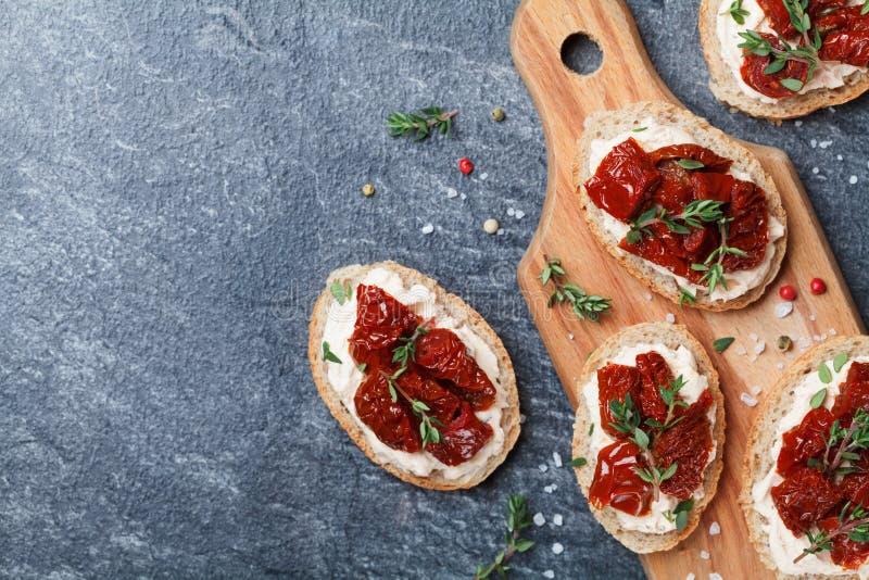 Panez les tranches avec le fromage fondu et les tomates séchées au soleil sur la vue supérieure en bois de table Casse-croûte et  photographie stock libre de droits