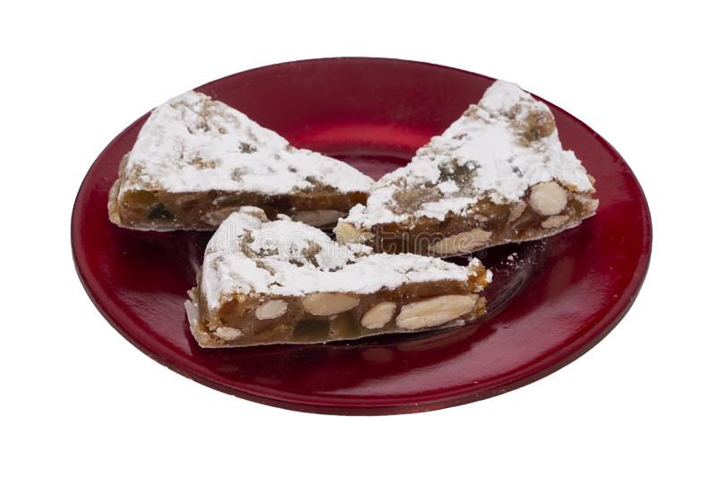Panforte-Scheiben auf der roten Platte, lokalisiert auf Weiß Italienische Weihnachtssüßspeise, -kuchen mit Trockenfrüchten machen lizenzfreie stockfotografie