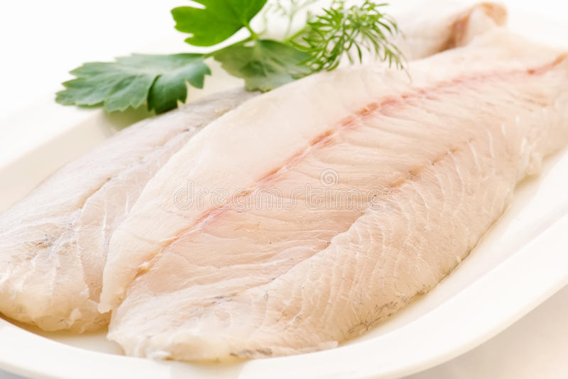 Pangasius Filet. Raw with herbs on a white plate stock photo