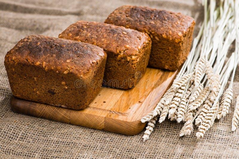 Pani di segale rustici casalinghi con i semi su un tagliere di legno, fotografia stock