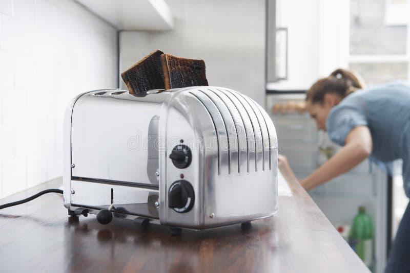 Pani tostati bruciati in tostapane con la donna nel fondo immagine stock