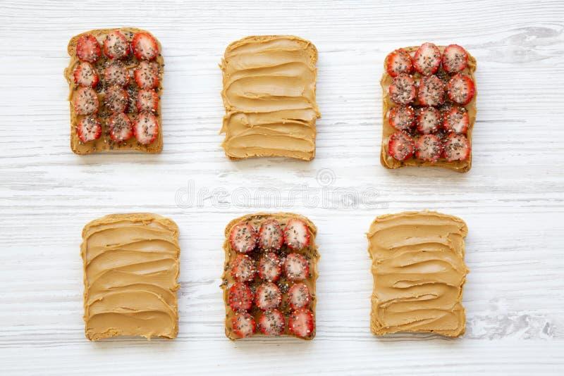 Pani tostati con burro di arachidi, le fragole ed i semi di chia su un fondo di legno bianco, vista superiore immagine stock