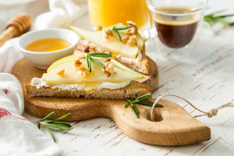 Pani tostati con la pera, il formaggio di capra e le noci, miele, rosmarino immagini stock