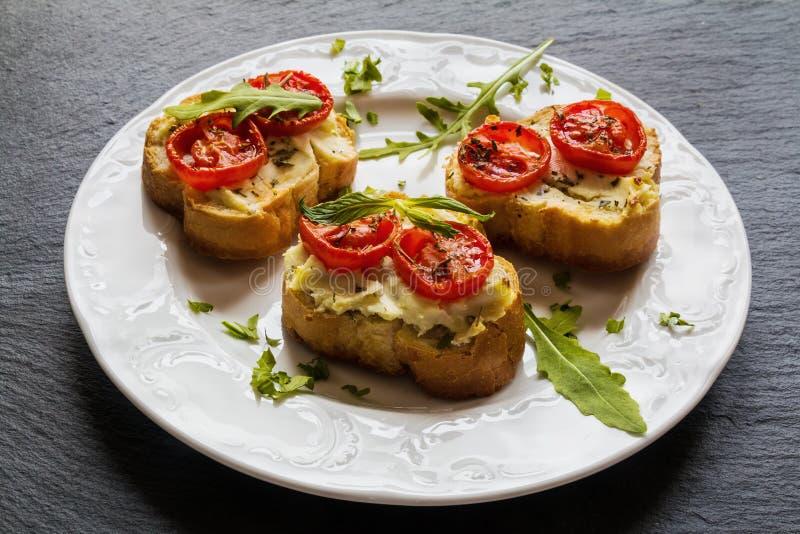 Pani tostati (Crostini) con la ricotta, i pomodori ciliegia e la rucola immagine stock