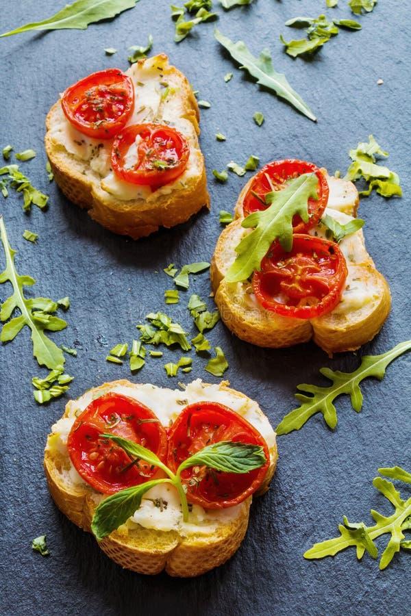 Pani tostati (Crostini) con la ricotta, i pomodori ciliegia e la rucola fotografie stock libere da diritti