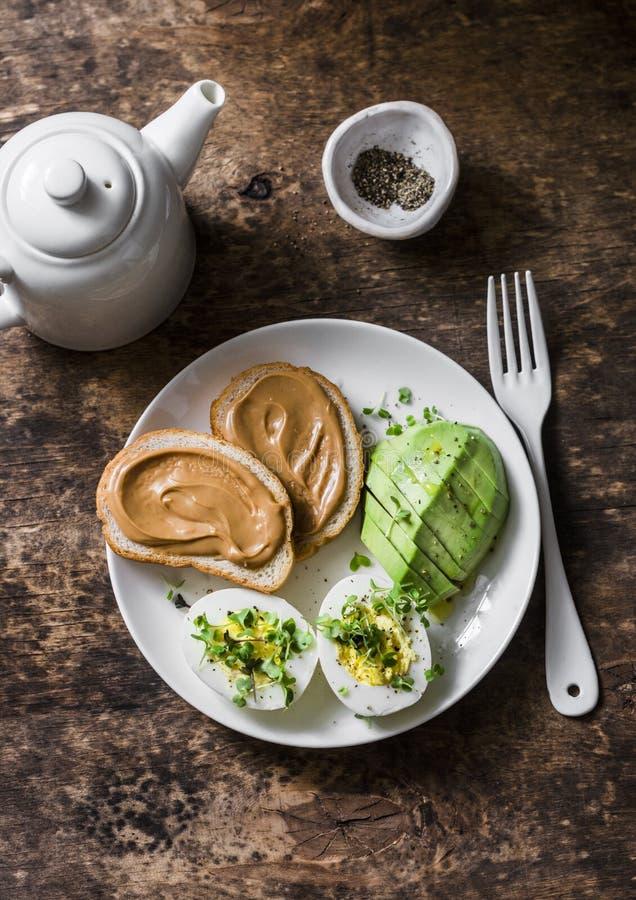 Pani tostati del burro di arachidi, uovo sodo con i micro verdi, avocado - prima colazione sana o spuntino su un fondo di legno fotografia stock libera da diritti