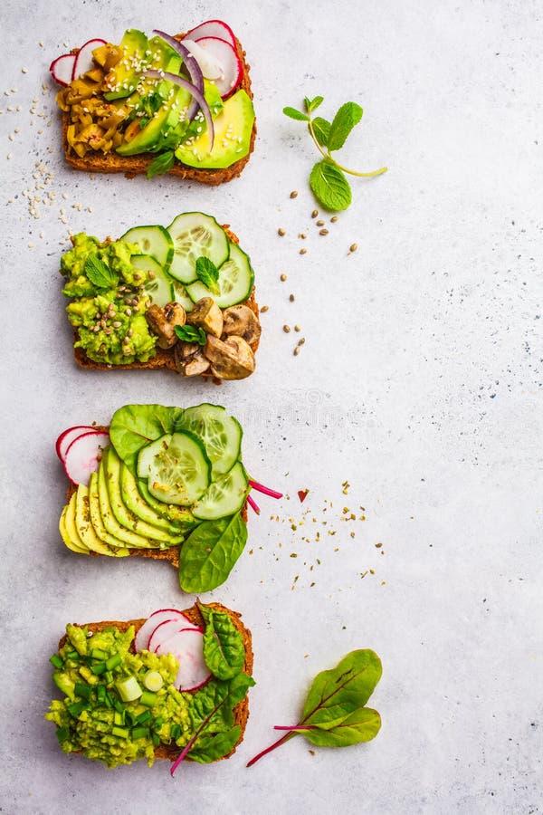 Pani tostati dell'avocado con differenti guarnizioni, vista superiore, backgrou bianco fotografia stock