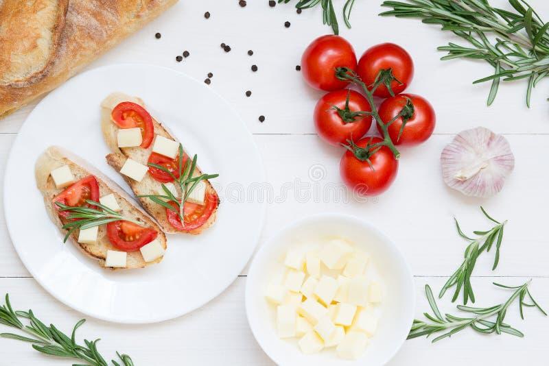 Pani tostati di Bruschetta con la mozzarella, i pomodori ciliegia ed i rosmarini freschi del giardino Vista superiore con spazio  immagine stock libera da diritti