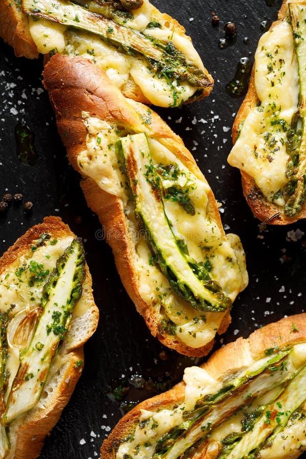 Pani tostati grigliati, Bruschetta con l'aggiunta di formaggio fuso, asparago verde, olio d'oliva ed erbe su un fondo nero, vista immagine stock libera da diritti