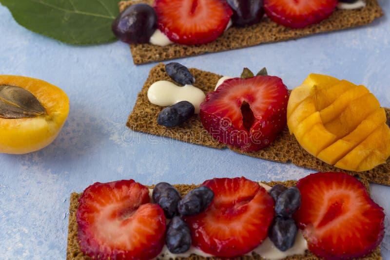 Pani tostati sani e saporiti con la ricotta, i frutti e le bacche su un fondo blu immagine stock libera da diritti