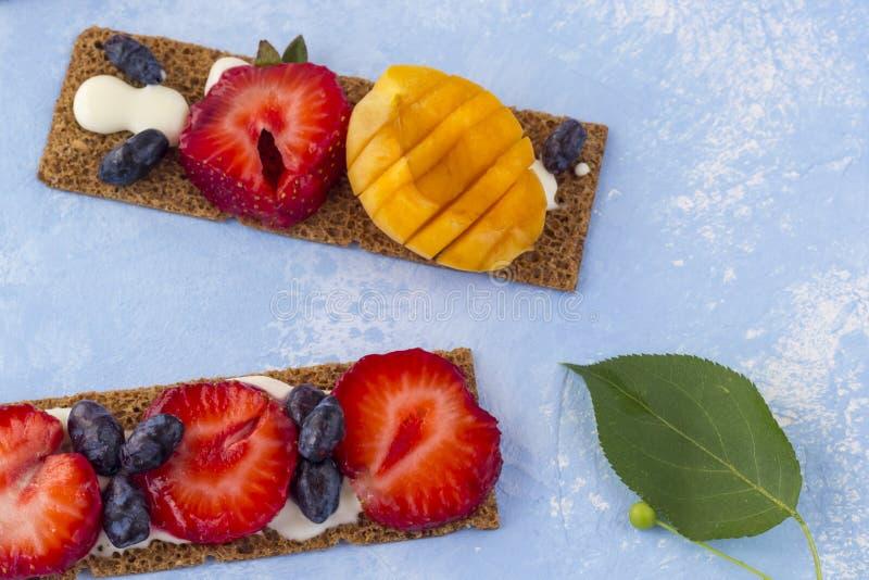 Pani tostati sani e saporiti con la ricotta, i frutti e le bacche su un fondo blu immagini stock