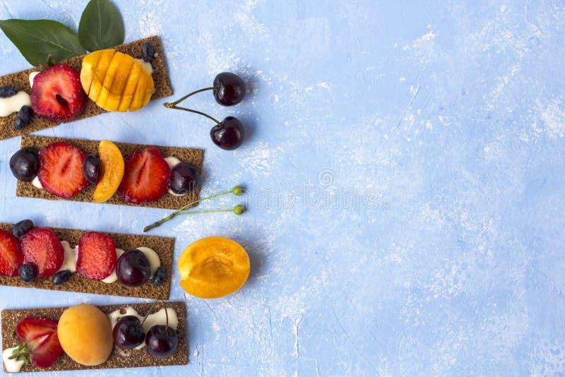 Pani tostati sani e saporiti con la ricotta, i frutti e le bacche su un fondo blu fotografia stock