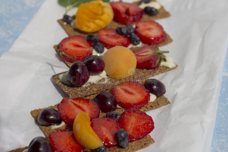 Pani tostati sani e saporiti con la ricotta, i frutti e le bacche su una carta pergamena bianca fotografie stock