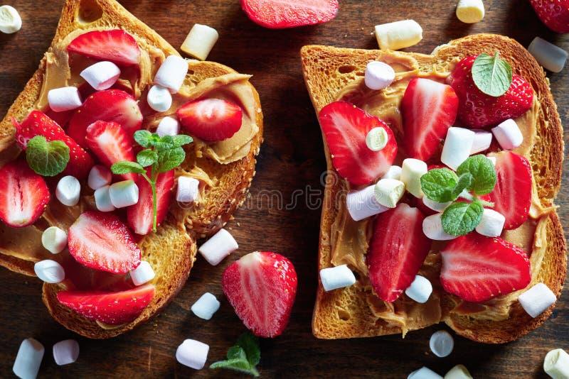 Pani tostati saporiti con burro di arachidi e le fragole immagini stock libere da diritti