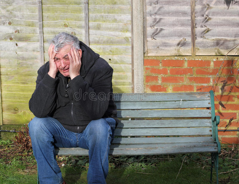 Panic attack man crying on a bench. stock image