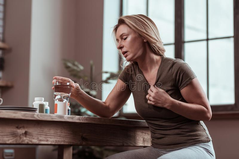 Blonde woman suffering from panic attacks taking pills. Panic attacks. Blonde-haired mature woman suffering from many panic attacks taking pills and drinking royalty free stock photos