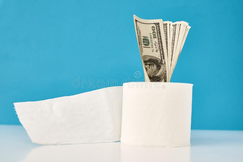Panic buying Covid-19 Coronavirus outbreak concept. Roll of toilet paper with usd dollar bills on a blue background stock image