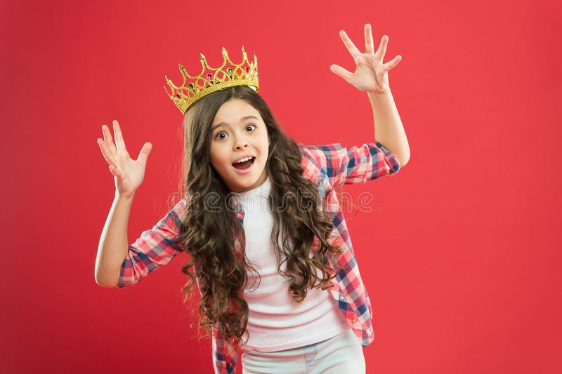 In panic. Scared little champion. Crowned champion with crown on red background. Funky small child got champion tittle royalty free stock photos