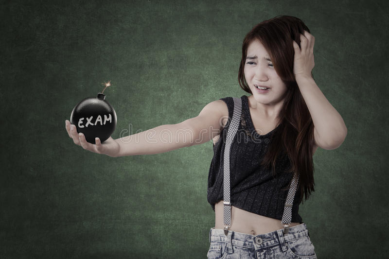 Panic student holding a bomb with exam text stock photo