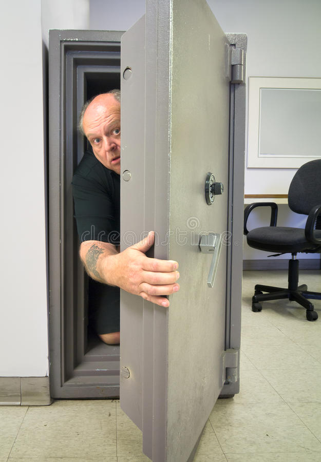 Panic Vault Room. A cowardly man crawling inside a vault in hopes of finding a secure and safe haven royalty free stock image