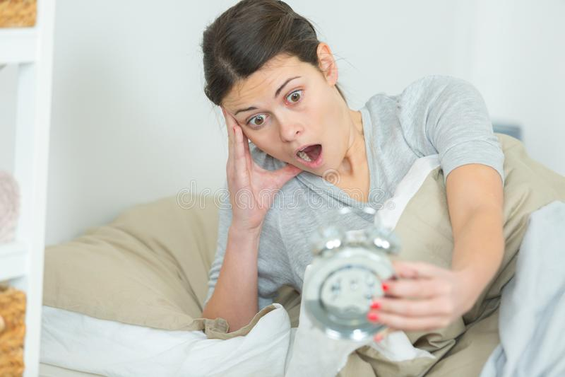 Panic woman waking up late in morning stock photos