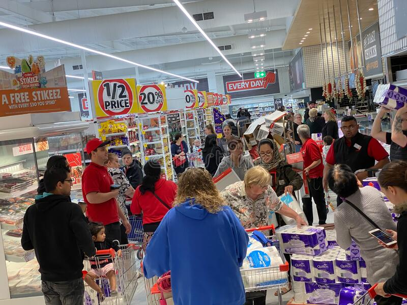 Panicked buyers grabbing toilet paper off the pallet. Narre Warren, Victoria Australia - March 6th 2020 - Panicking customers in a supermarket buying toilet royalty free stock photography