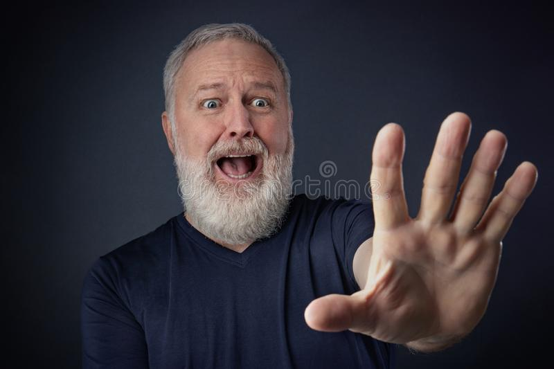 Panicked elderly man with his stretched hand forward royalty free stock image