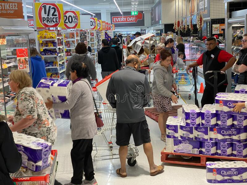 Panicked shoppers grabbing toilet paper off the pallet. Narre Warren, Victoria Australia - March 6th 2020 -Panicking customers in a supermarket buying toilet stock image