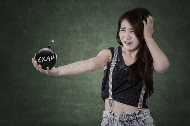 Paniekstudent die een bom met examentekst houden stock foto
