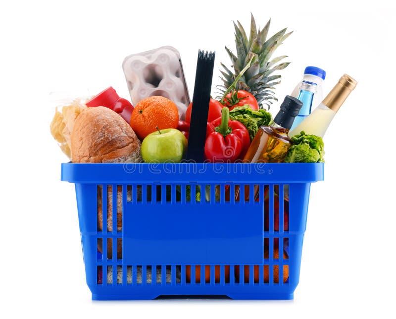 Panier à provisions en plastique avec les produits assortis d'épicerie photographie stock libre de droits