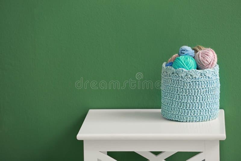 Panier avec des boules de fil à tricoter sur la table sur le fond de couleur photographie stock