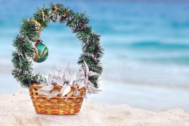 Panier avec des décorations de Noël sur une plage à la région de la mer photo stock