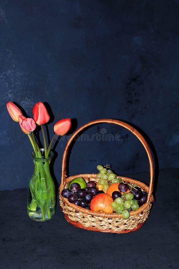 Panier avec des pommes, des tulipes et des raisins sur un vieux fond abstrait, foyer sélectif photos libres de droits
