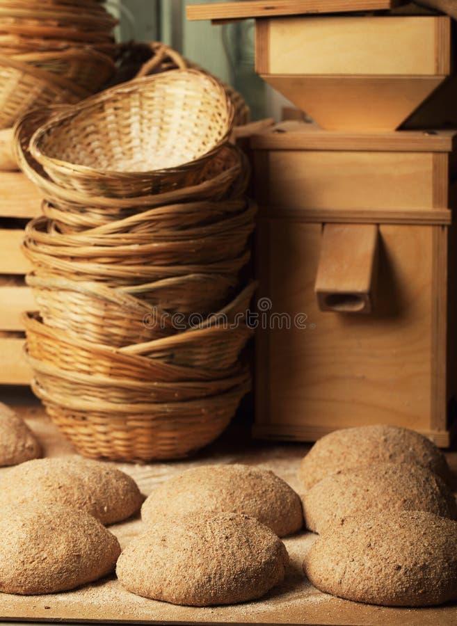 Panier avec la pâte de pain et un petit moulin photo stock