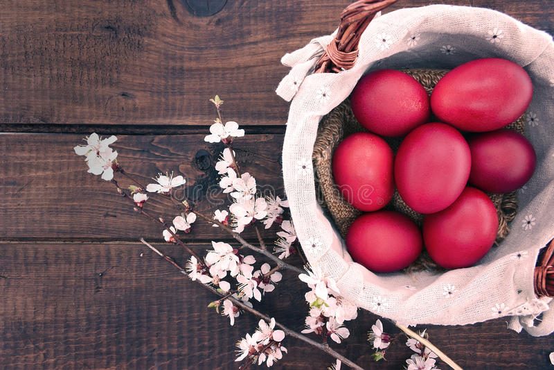Panier avec le gâteau de Pâques et les oeufs rouges sur la table en bois rustique dessus photo libre de droits