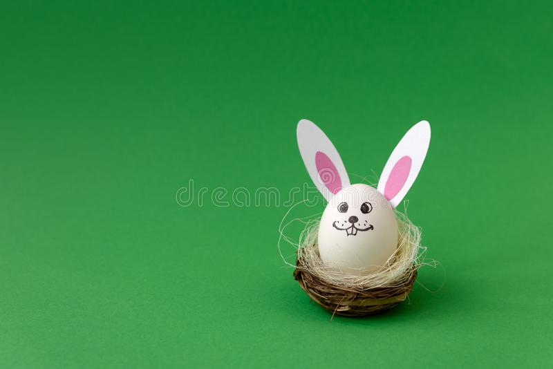 Panier avec le lapin de Pâques fait à partir des oeufs et des oreilles de papier sur le fond en pastel vert idée créatrice Concep photographie stock