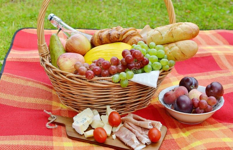 Panier avec le pique-nique de boulangerie de fruit de nourriture photographie stock libre de droits