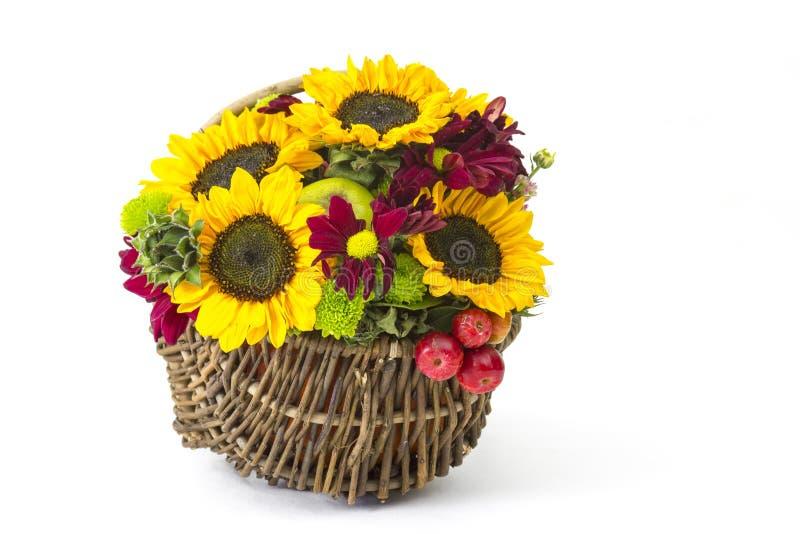 Panier avec les fleurs, les baies et les pommes automnales image libre de droits