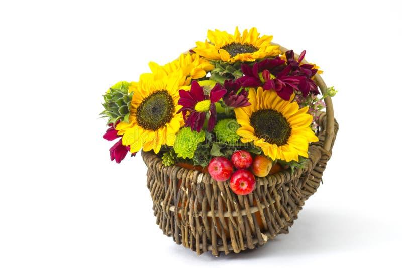 Panier avec les fleurs, les baies et les pommes automnales photos libres de droits