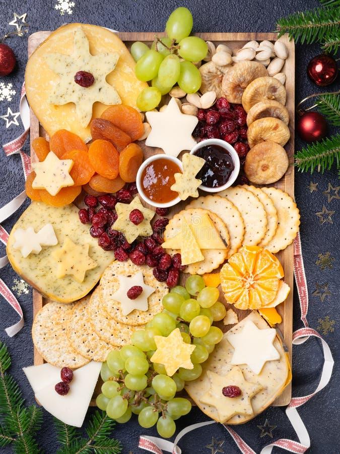Panier d'amuse-gueule de Noël en carton de fromage avec divers types de fromage, craquelins, confiture, fruits et pistaches Vue d photographie stock