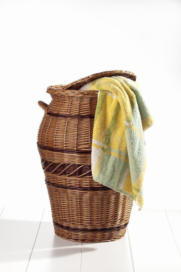 Panier de blanchisserie avec la serviette sur le fond blanc images stock