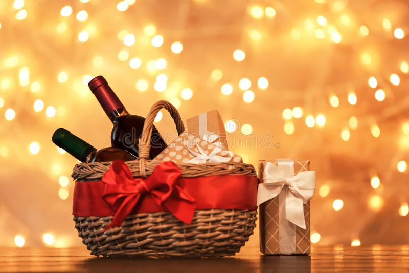 Panier de cadeau avec des bouteilles de vin contre les lumières brouillées photo libre de droits