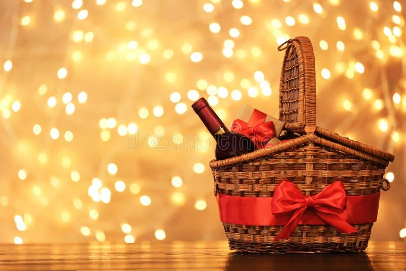 Panier de cadeau avec la bouteille de vin contre les lumières brouillées photo libre de droits