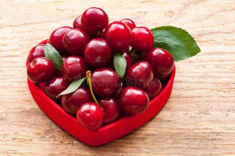 Panier de cerise dans la cuvette rouge Cerise avec des feuilles au coeur Merises fraîches photo libre de droits